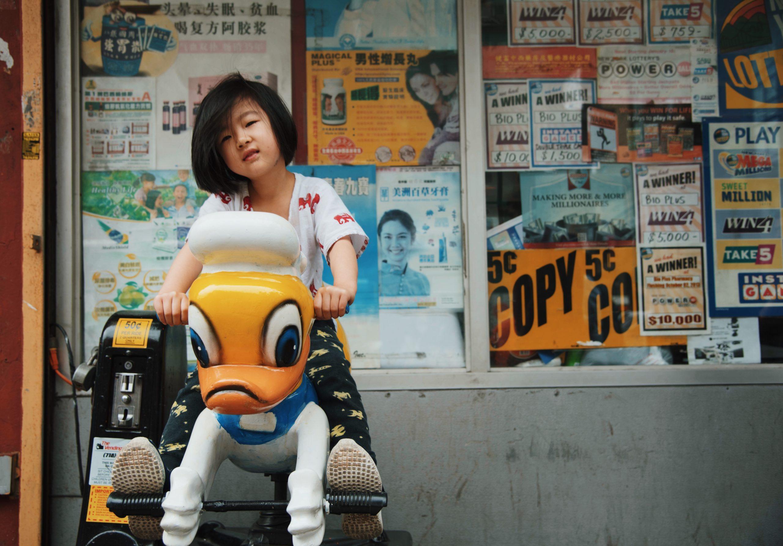 girl riding a Donald Duck arcade