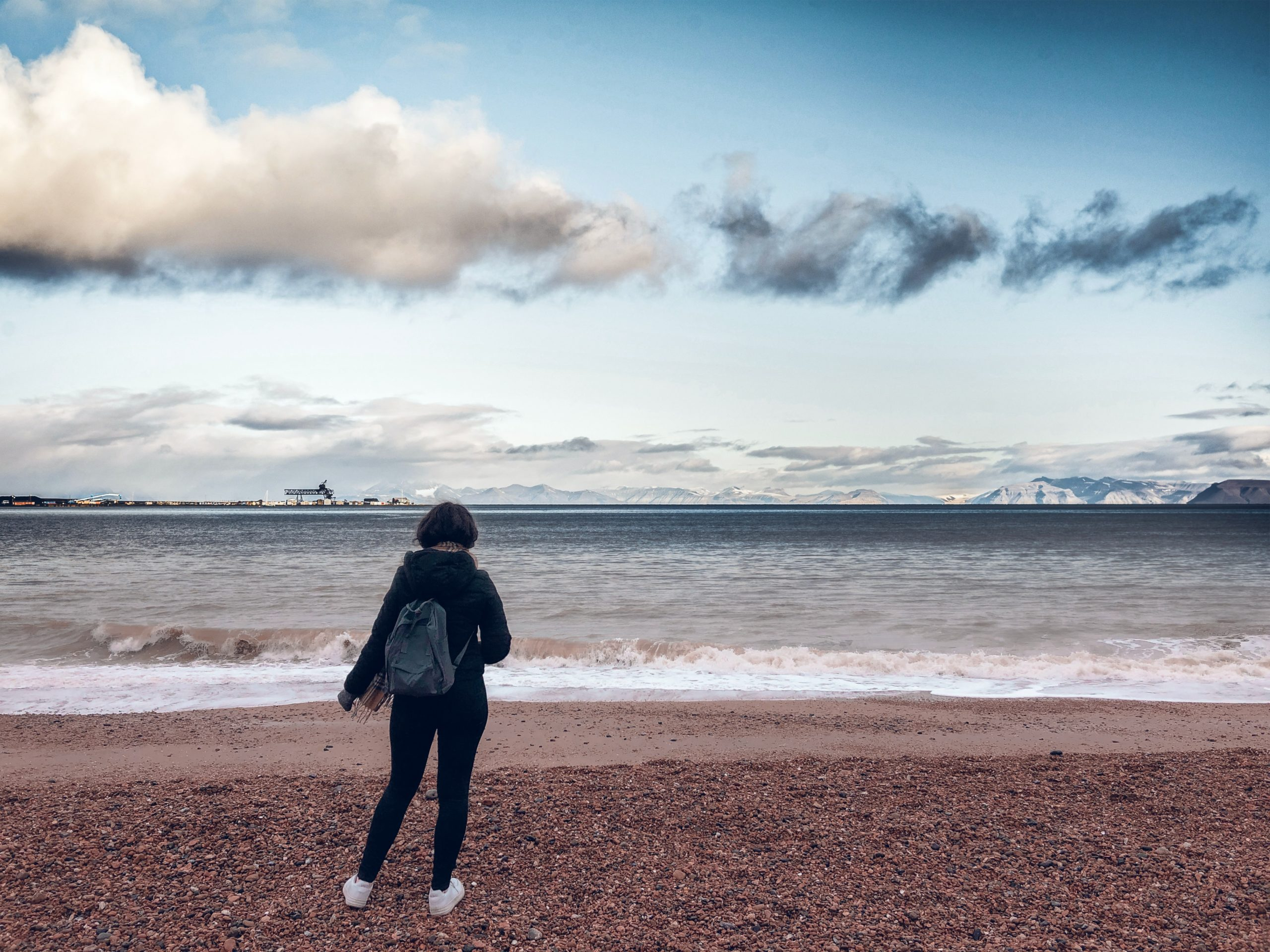 woman in black jacket and black pants standing on seashore during daytime