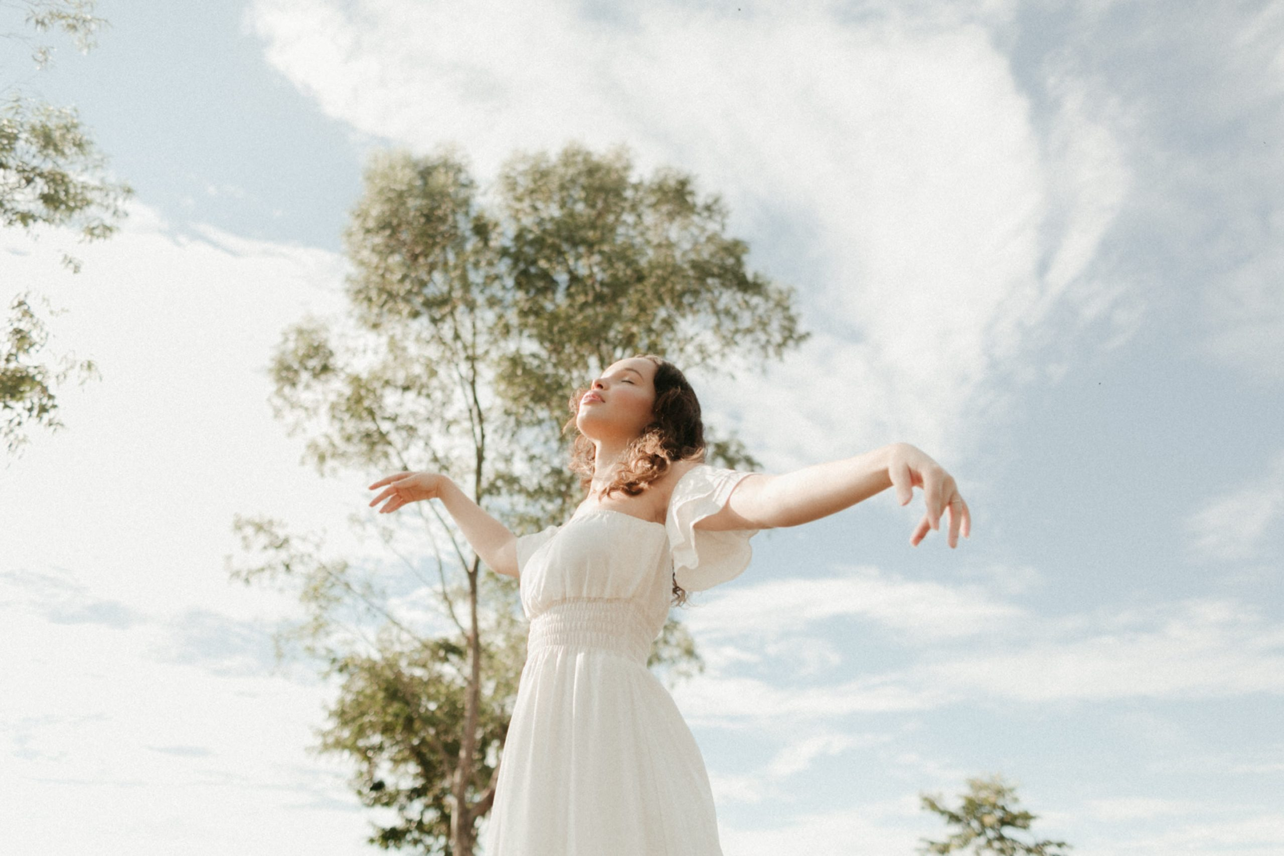 woman in white dress standing and raising her hands
