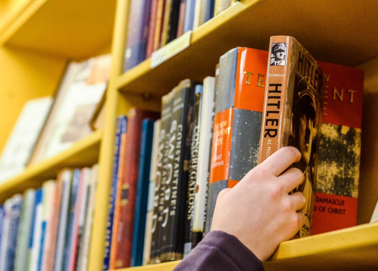 person holding book in book shelf